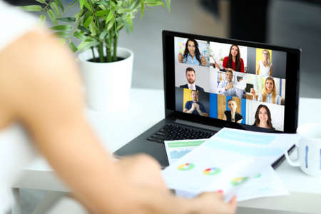 Woman talking with international colleagues using online video chat service at workplace closeup Banco de Imagens