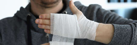 Close-up of male person bandaging hand with medical bandage. Increase blood circulation and relieve pain. Preventing repeated injury. Medicine and health prevention concept