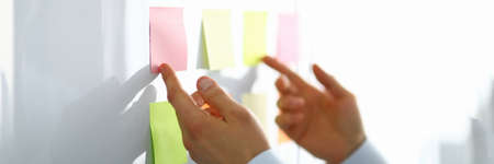 Close-up of worker hand holding colorful papers for notes with information. Person preparing for conversation of directors. Business and company concept