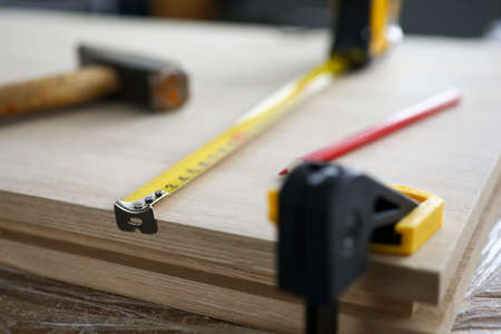 Close-up of carpenter tools and instruments for joinery work. Wooden plank fixing in vise, measuring tape, hammer and pencil. Carpentry workshop concept