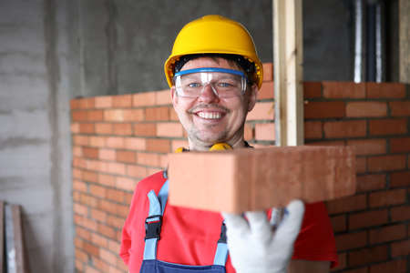 Happy builder holds brick for masonry and smiles. Red brick masonry. Calculation amount necessary building materials. Developer is building residential houses. Brick is used to lay foundation Stockfoto