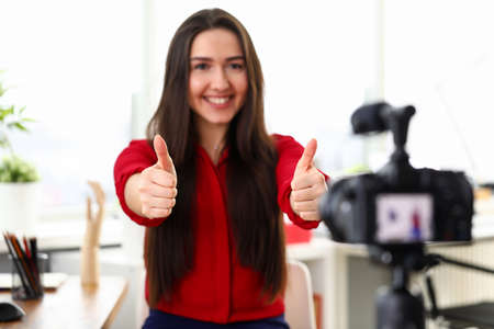 Office worker girl showing ok in front camera. Girl sitting in front camera smiles on blog. Girl welcomes her subscribers. Implementation interaction with team through corporate video blog 免版税图像