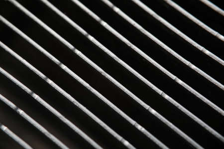 Dark gray metal grating in low light technique close-up