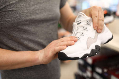 Close-up of persons hands holding stylish white sneakers. Male wearing grey shirt. Man choosing shoes for run and sport. Shopping in trading centre concept