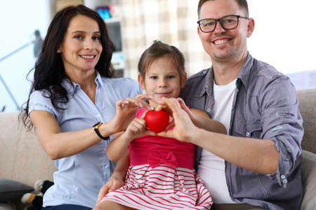 Portrait of cheerful lovely parents and little kid holding red heart together. Cheerful daughter sitting on father knees and smiling sincerely. Happy family concept
