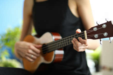 A woman in a black dress is learning to play the ukulele. Girl tunes a miniature guitar before a concert