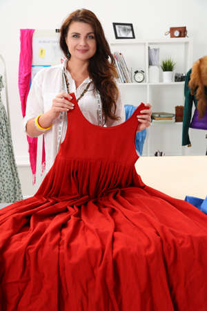 Tailor shows her painstaking work in pleated dress. Woman smiles and demonstrates her project for passing exam on course. Young designer recreates fashion past centuries, noble dress