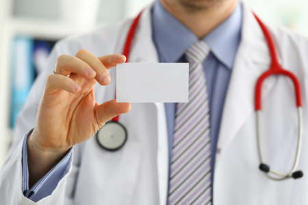Male medicine doctor hand holding blank calling card. Physician showing white visiting card in camera closeup. Contact information exchange concept. Introducing gesture at formal meeting 免版税图像