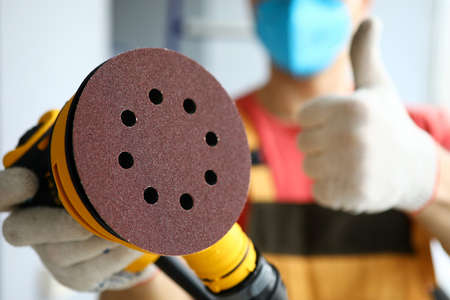 Close-up of sander in hands of builder showing ok or good gesture. Handyman with sandpaper appliance, tool for working at construction site. Workman with instrument