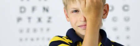 Portrait of child closing one eye with hand. Kid on eye doctor appointment in clinic. Board with letters on background. Ophthalmologist cabinet. Medicine and healthcare concept
