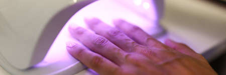 Woman dries nails with manicure in a professional UV lamp close-up. The final stage of manicure