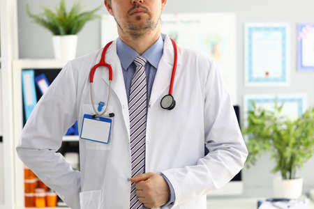 Stethoscope lying on male therapeutist doctor chest wearing necktie. Medical care help or insurance equipment shop or store concept. Physician waiting for patient to examine Stok Fotoğraf