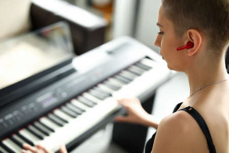 Close-up of talented female playing on synthesizer. Modern instrument for musician. Short haired young woman performing melody on piano. Music and hobby concept Zdjęcie Seryjne