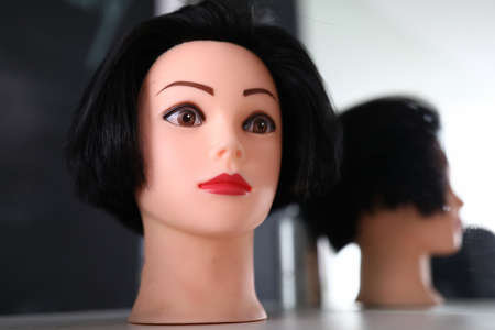 Close-up of mannequin head of woman. Female face with makeup. Practice for hairdresser. Plastic head model with short hairstyle and reflection in mirror