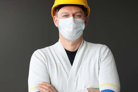 Male construction worker in yellow caste and medical protective mask. Coronavirus pandemic construction concept
