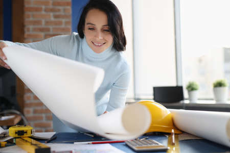 Smiling woman designer in her office. Development of design of apartments and houses concept
