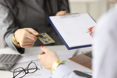 Employee gives the client plastic bank card and document for signature. Banking services concept