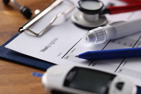 On table is blood glucose meter and daily monitoring schedule. Diabetes mellitus daily sugar control concept