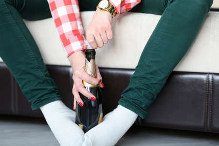 Woman holding bottle of champagne with her feet and opens it closeup. Celebrating alone concept