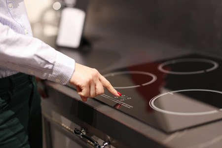 Female finger presses button on touch electric stove. Sale of household appliances koncetp