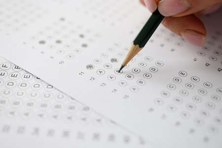 Woman solving tests and writing in pencil on paper closeup. Exam testing concept