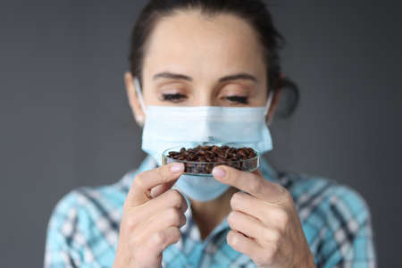Woman in protective medical mask sniffs coffee grains. Loss of smell in coronavirus concept 版權商用圖片