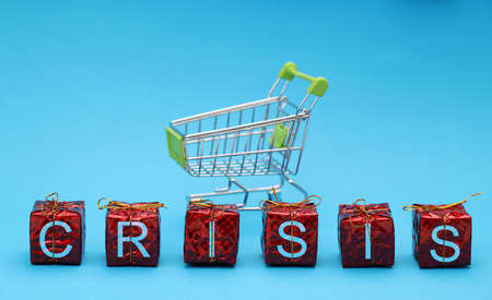 Shopping basket next to cubes with inscription crisis. World economic crisis concept