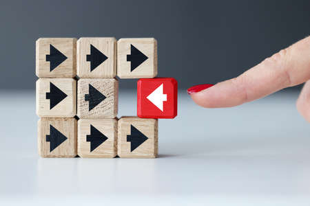 Wooden cubes with black arrows and one red one. Individual approach in business concept