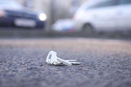 Bunch of keys lies on road in parking lot. Key recovery service concept Standard-Bild