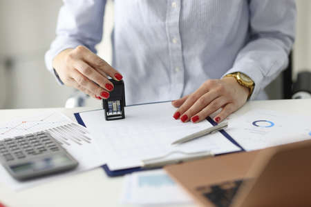 Woman with red manicure putting stamp on documents in office. Signing contract concept