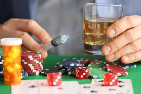 Male hands are holding syringe with needle and glass with alcohol next to casino chips. Addictions and their treatment concept