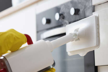 Hands in rubber gloves washing facades in kitchen with steamer closeup. Living quarters cleaning concept