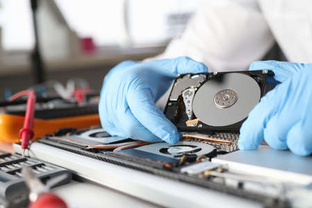 Gloved master holds a hard drive. Diagnostics and repair of computer equipment concept