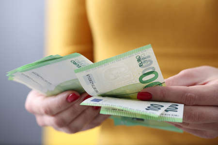 Woman is counting one hundred euro bills. Payroll concept