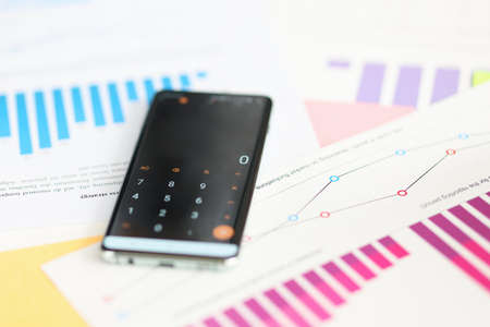Phone with included calculator lying on documents in office closeup. Profit growth concept