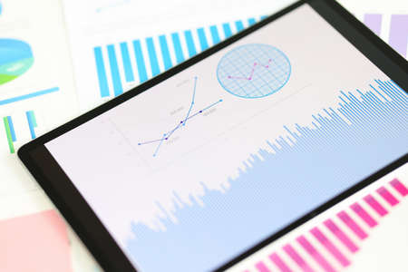 Digital tablet with graphs and charts lying on documents closeup. Business statistics concept