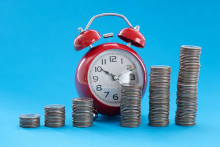 Coins stacked in ascending order standing against background of alarm clock. Successful business increase in earnings concept Stockfoto