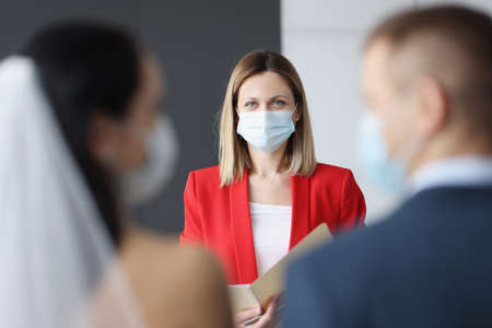 Wedding ceremony in which bride and groom together with receptionist in medical protective masks.