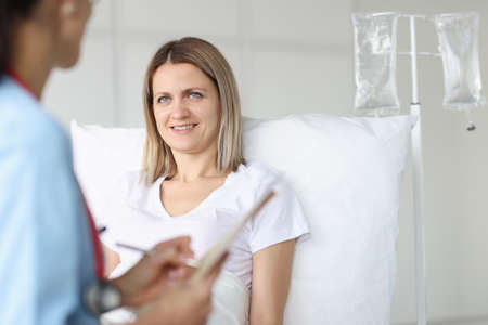 Doctor examining woman lying on bed in hospital. Infusion therapy concept