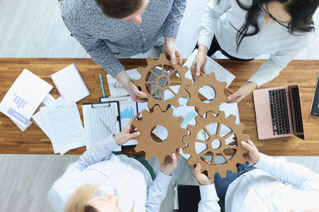 Employees in office connect gears in place. Business team building concept