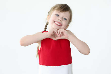 Little girl showing heart shape with her hands