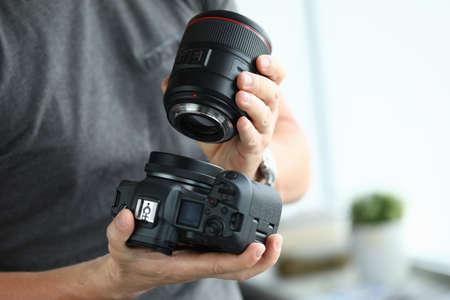 Male hands putting on modern digital camera professional lens
