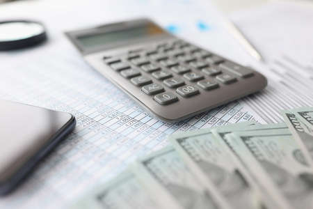 American banknotes, along with financial statement and calculator, lie on table Imagens