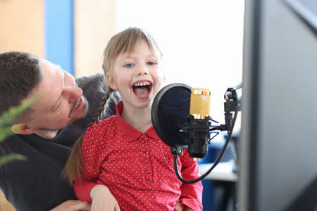 Little girl sitting on her fathers lap and singing song into microphone