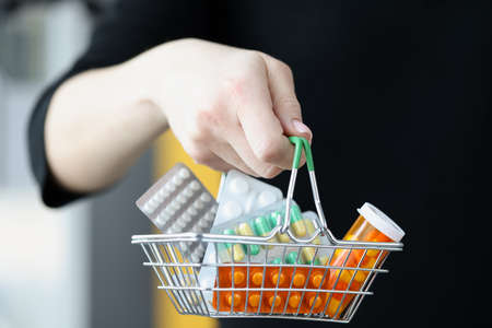 Woman holding basket of medicines in her hand closeup