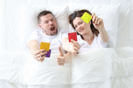 Man and woman lying in bed and holding condoms top view