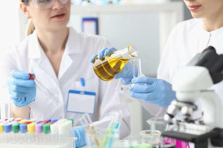 Two researchers in laboratory examine golden liquid in test tube Foto de archivo
