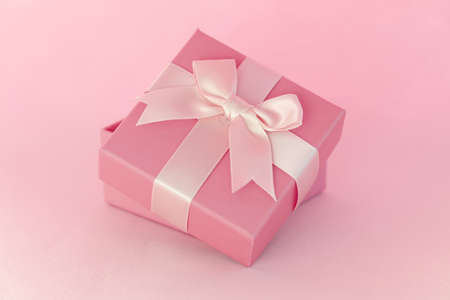 Beautiful gift with bow standing on blue background