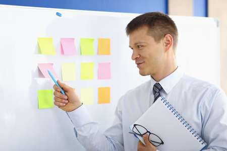 Portrait of male person pointing pen on colorful notes on marker board