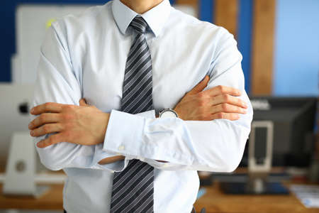 Close-up of businessman with folded hands. Male person having break at workplace